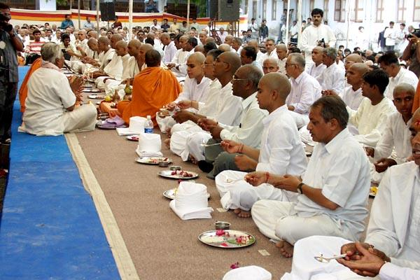 Sadhaks engaged in the parshad diksha rituals, with their parents besides them