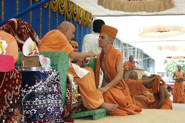 Swamishri gives diksha-mantra and initiates a parshad into the sadhu-fold