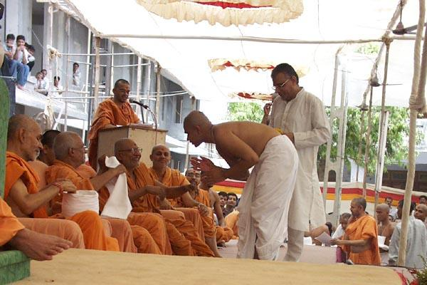 A youth being initiated into the parshad-fold. First he receives a new kanthi from a senior sadhu ...