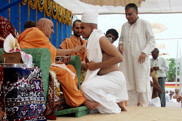 ... and finally Swamishri smears chandan on his forehead, chest and arms and gives him the diksha-mantra