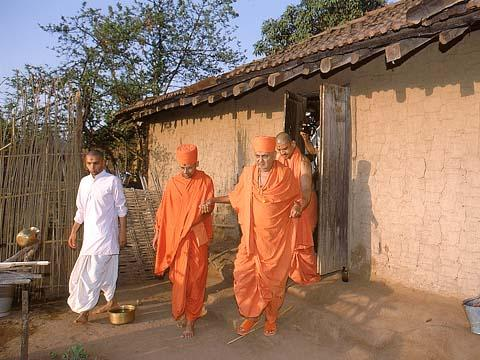 Swamishri, after sanctifying a tribal's hut, Jamlapada
