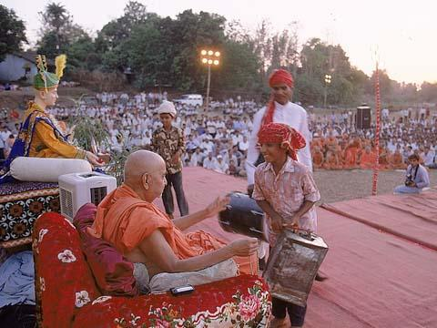 Swamishri blessing a satsangi tribal boy and his musical instrument, Dharampur
