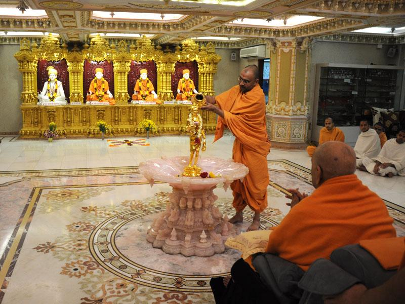 Swamishri engaged in darshan and abhishek of Shri Nilkanth Varni ...