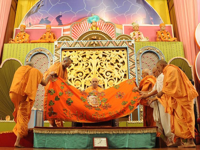 Sadhus honor Swamishri with shawl and garland