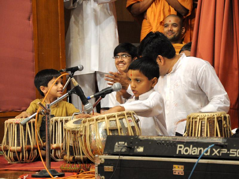 Swamishri showers his blessings and joy upon children playing tabla on stage