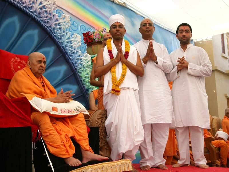 Swamishri with newly initiated parshad and his father and brother