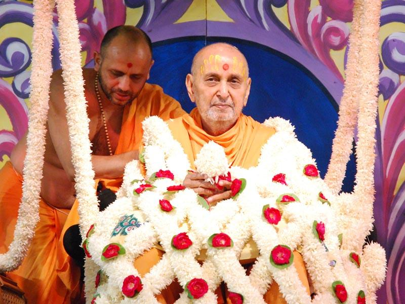 Sadhus honor Swamishri with a flower shawl