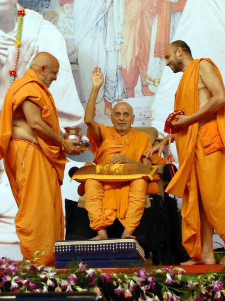 Sadhus honor Swamishri with a shawl and garland