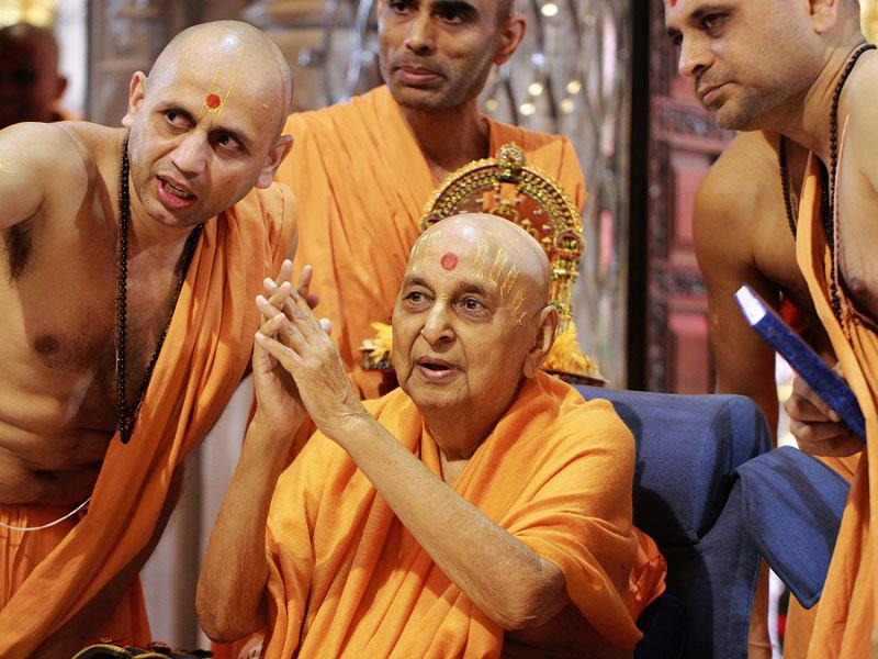 Swamishri in a divine mood bidding Jai Swaminarayan to devotees