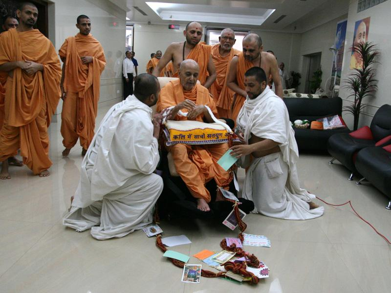 On behalf of the youths from USA, parshads honor Swamishri with a garland ...