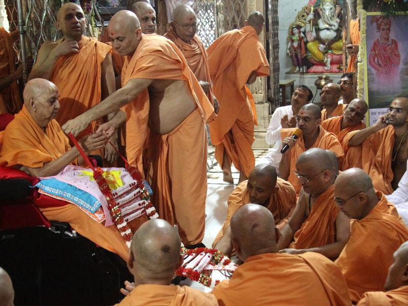 Senior sadhus honor Swamishri with garlands and a shawl