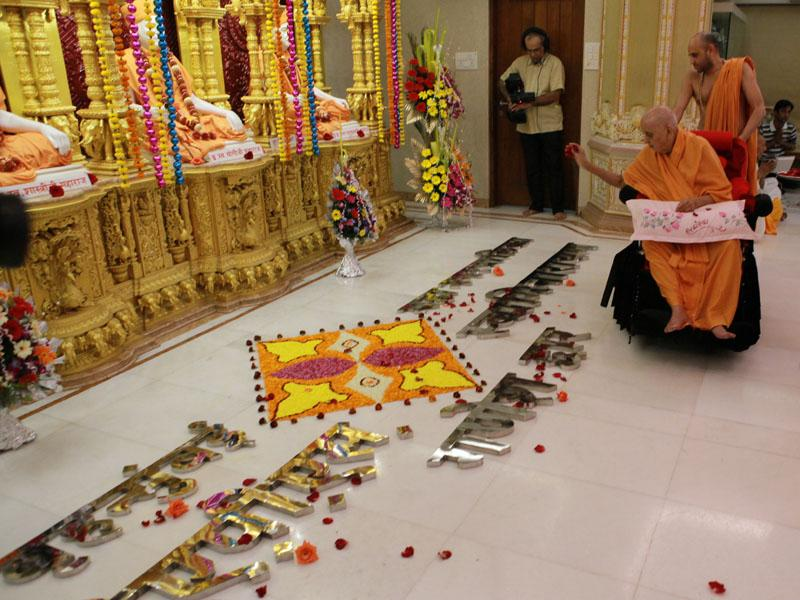 Swamishri sanctifies metallic letters to be set on the Ganesh Dwar