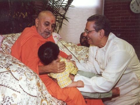 Swamishri blessing a young boy