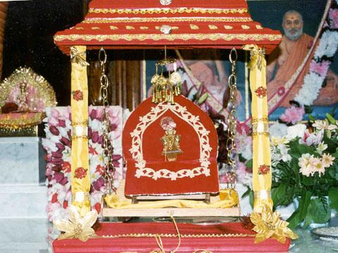 Harikrishna Maharaj swinging on a specially made hindolo initiating the month long hindolo festival