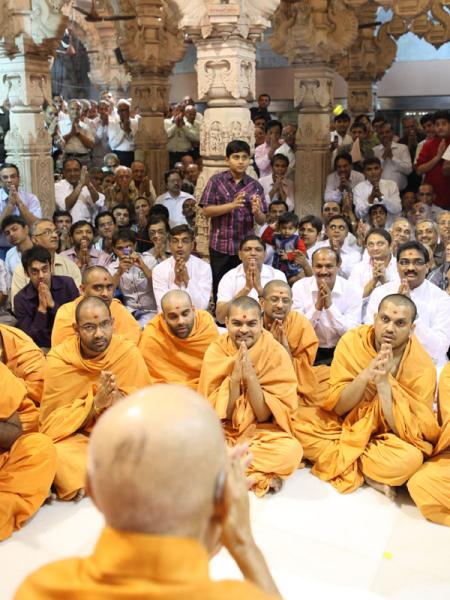 Devotees engaged in Swamishri's darshan beneath the mandir dome