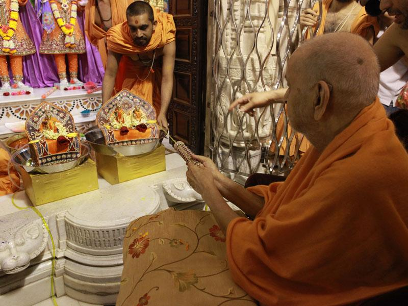 Swamishri sprays Thakorji with colored water