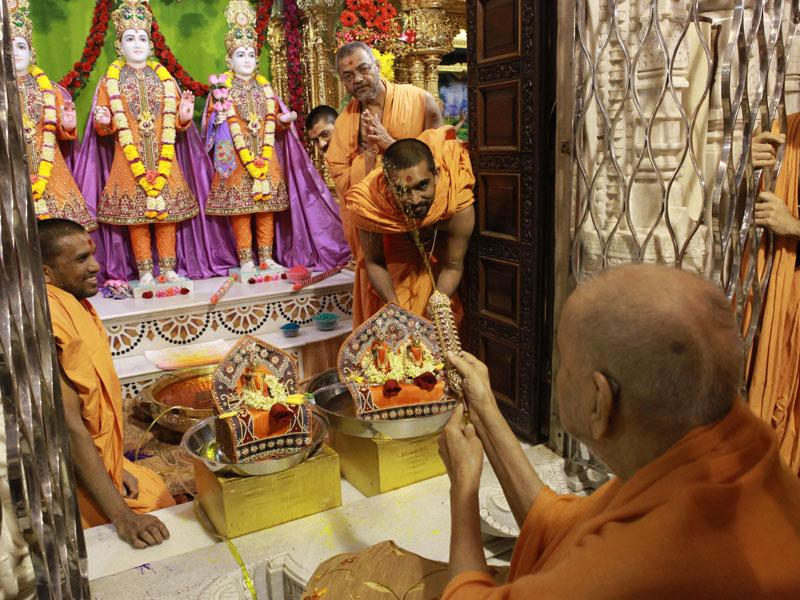Swamishri sprays colored water on sadhus
