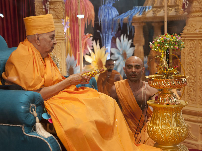 Swamishri sprays colored water on Shri Harikrishna Maharaj