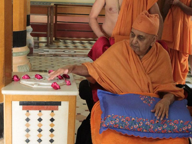 Swamishri reverentially touches holy charnarvind of Bhagwan Swaminarayan at Rang Mandap