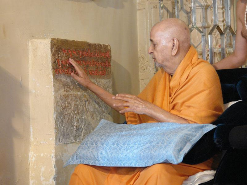 Swamishri reverentially touches stone sanctified for forty years in Junagadh by Aksharbrahman Gunatitanand Swami