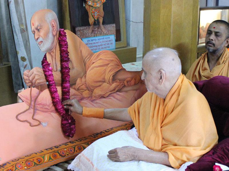 Swamishri sanctifies the painting of Shastriji Maharaj