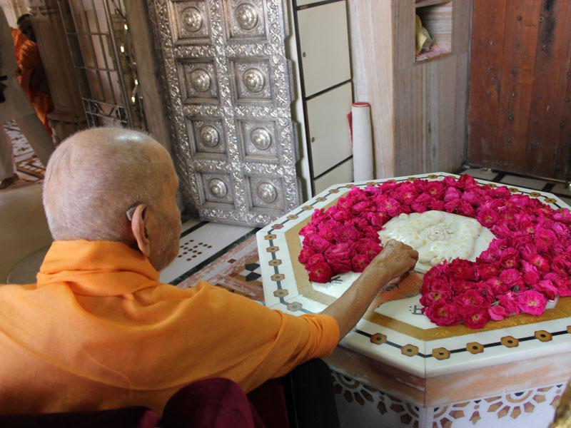 Swamishri reverentially touches the charanarvind at Smruti Mandir
