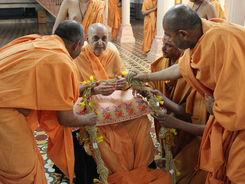 Sadhus honor Swamishri with a garland of malas