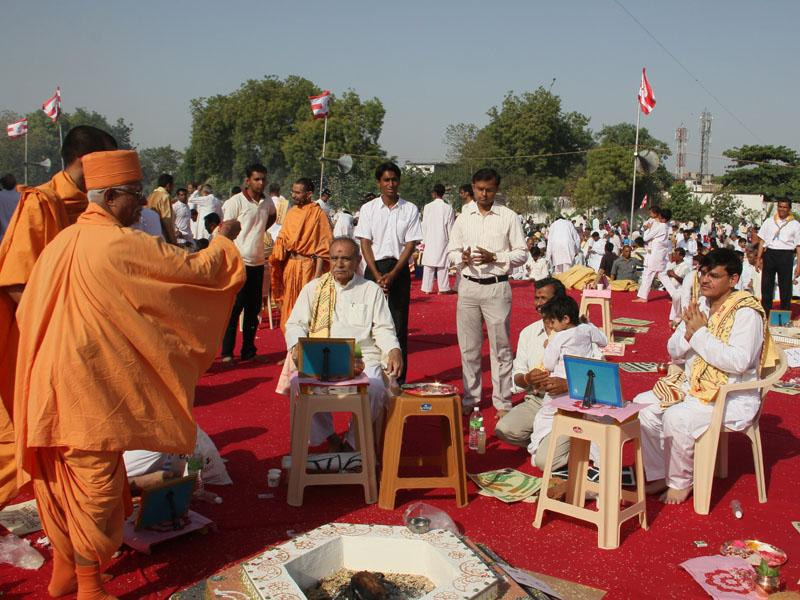 Pujya Doctor Swami blesses devotees by showering rice grains