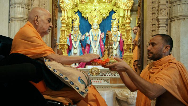 Swamishri touching Thakorji's feet with devotion
