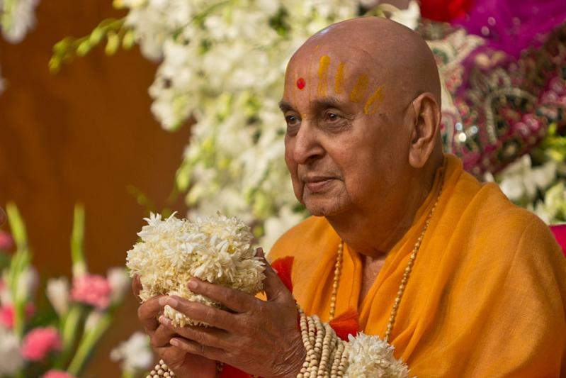 Swamishri is honored with garlands and a specially made bunch of flowers