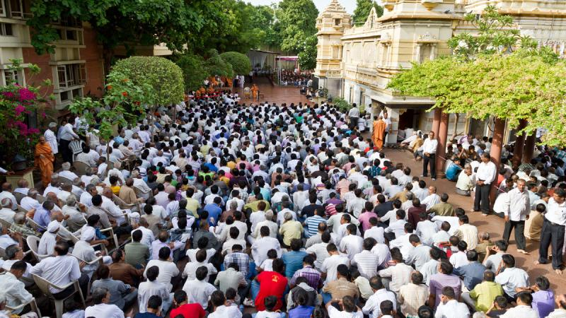 Devotees attend a sabha while waiting for Swamishri's darshan