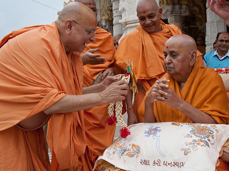 Pujya Ishwarcharan Swami ties a rakhdi on Swamishri's wrist, on behalf of all devotees