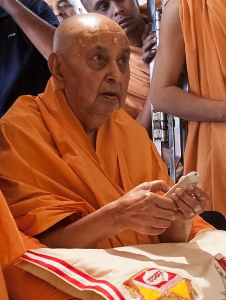 Swamishri uses a remote control to begin the flow of 'dudhpak' by Bhagwan Swaminarayan into Gunatitanand Swami's pattar