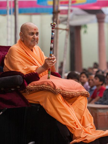 Swamishri gives darshan while holding a traditional Masai peace stick