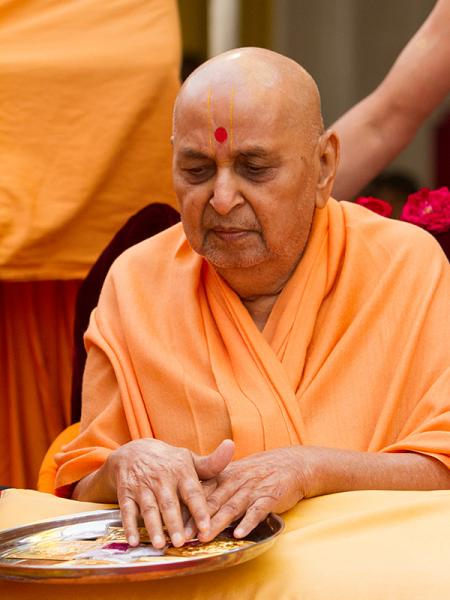 Swamishri sanctifies yantras to be place beneath the murtis