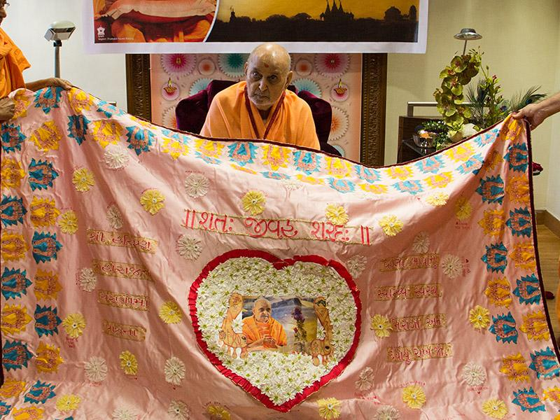 Senior sadhus honor Swamishri with shawls and garland