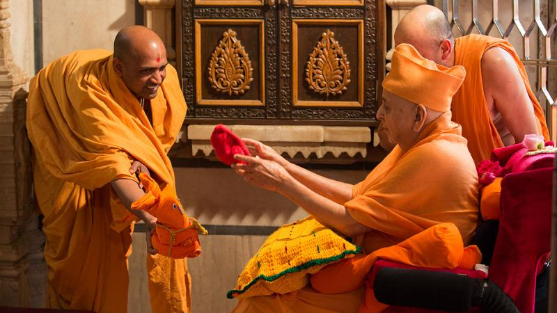 Swamishri sanctifies a ball made of cloth