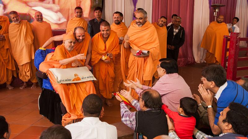 Swamishri sanctifies the decorated coconut and then tosses it back to the delighted devotees