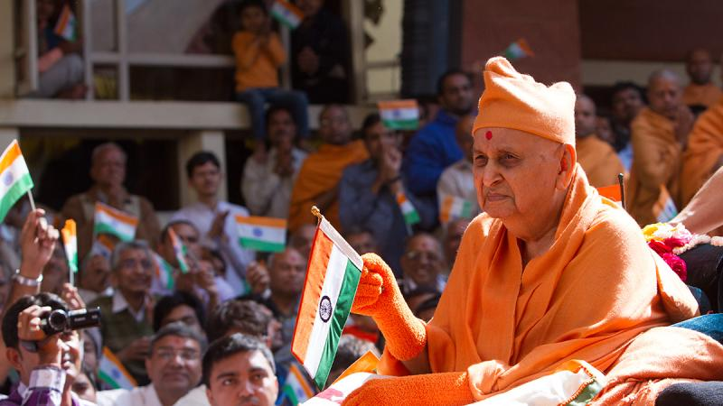 Swamishri greets devotees by waving the Indian tricolor