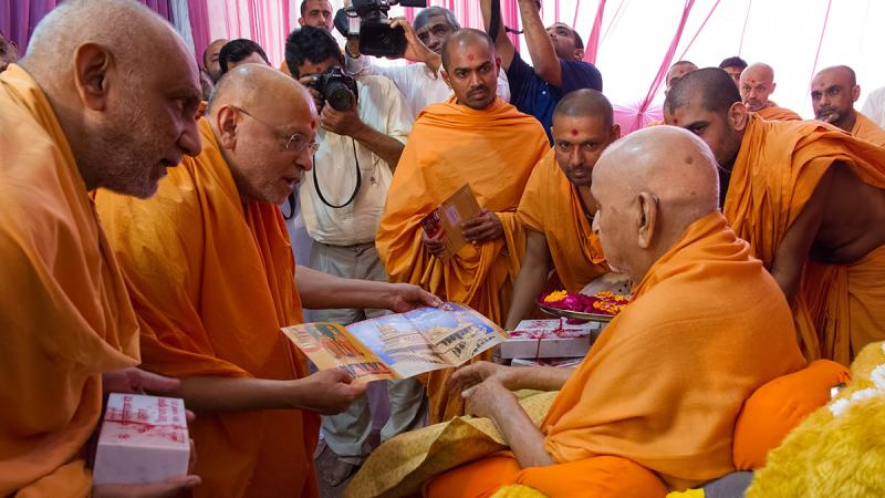Swamishri sanctifies invitation card of Shilanyas vidhi for BAPS Shri Swaminarayan Mandir at Jalandhar, Punjab, India