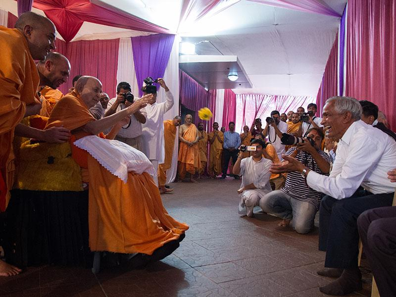 Swamishri sanctifies a flower and tosses it to a devotee