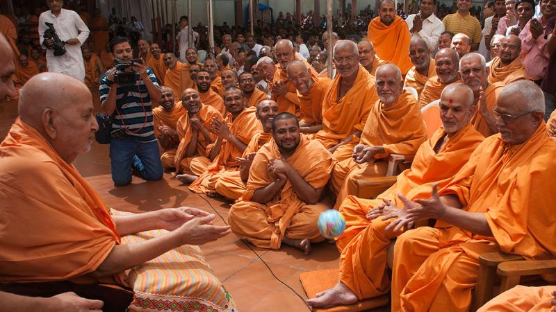 Swamishri tosses the ball to Pujya Swayamprakash Swami (Doctor Swami)