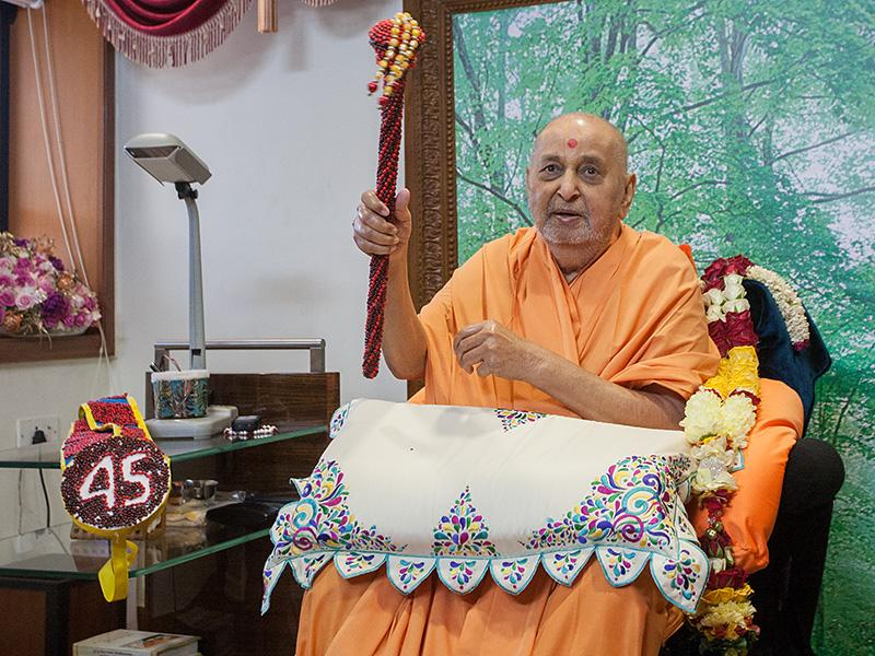Swamishri sanctifies a traditionally decorated stick