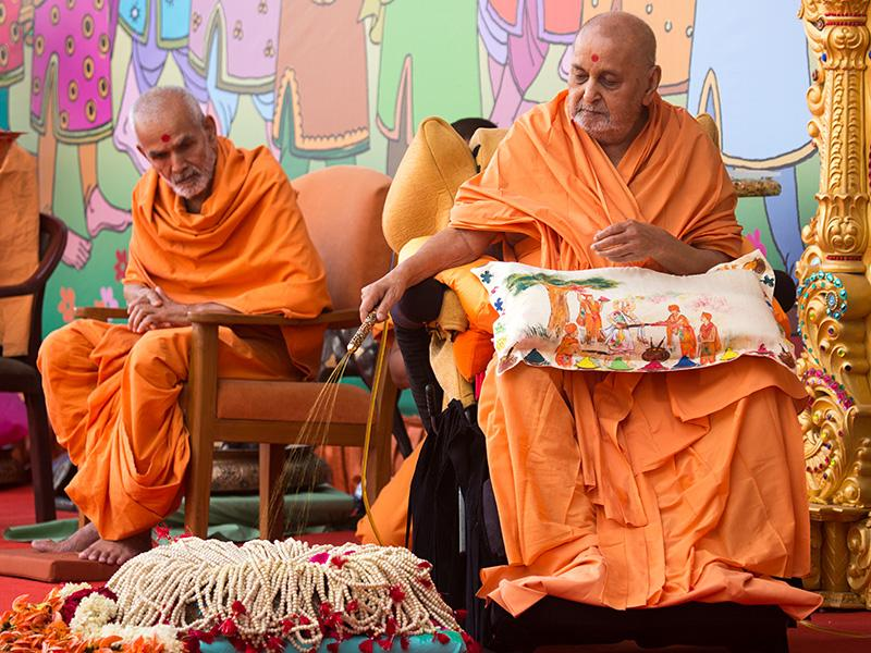 Swamishri sanctifies malas by spraying colored water