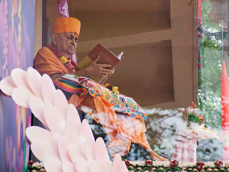 Swamishri sanctifies the set by browsing through one of the books after the inauguration