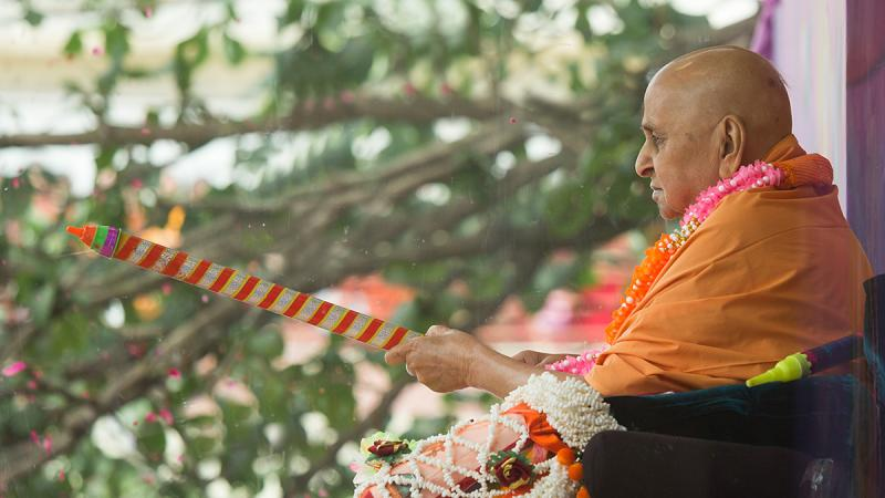 Swamishri with a water jet in his hands, signifying playing with colors on the festival of Holi
