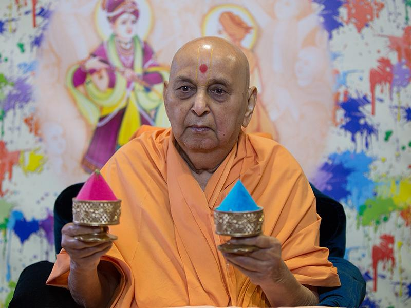 Swamishri holds up colored powders to signify the festival of colors