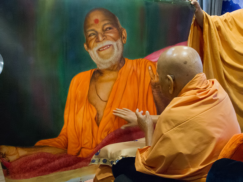 Swamishri sanctifies a painting of Brahmaswarup Yogiji Maharaj