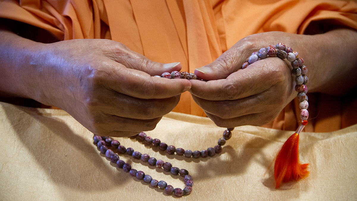 Swamishri sanctifies a 'Vaijayanti mala' made by sadhus with prayers written on each bead