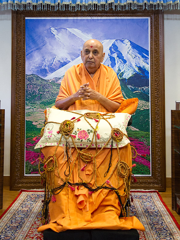 Swamishri is honored with a shawl of malas